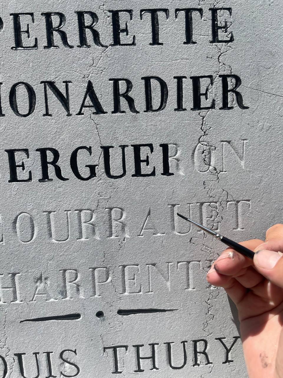 Travaux de peinture à la brosse filet pour réécrire les noms à la mémoire des défunts